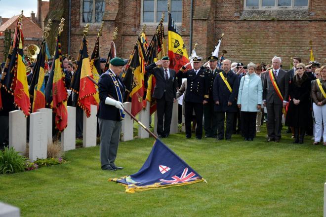 vlaggendrager brengt hulde terwijl alle anderen groeten